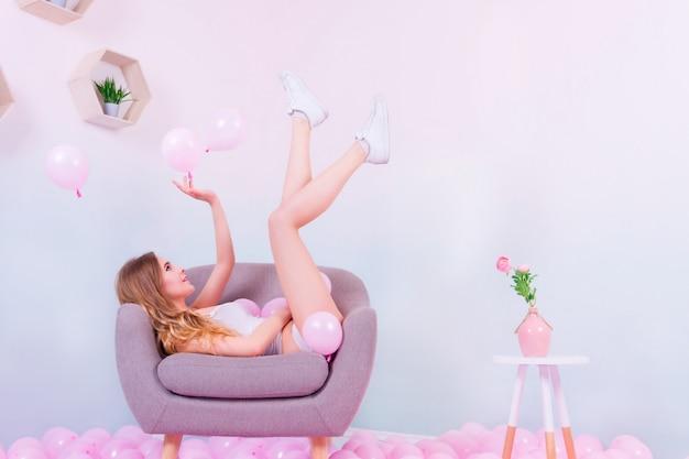 Chica en ropa interior blanca y zapatillas blancas jugando con globos rosados