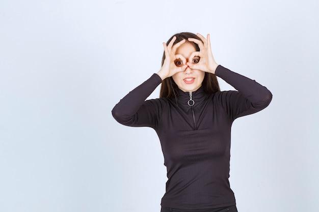 Chica en ropa negra mostrando signo de disfrute del círculo.