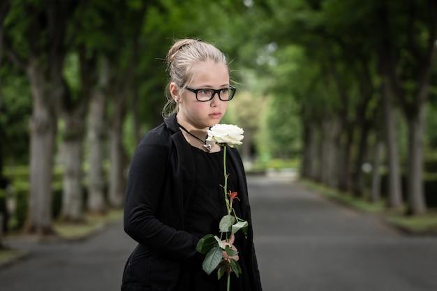 Chica con rosa blanca de luto fallecido en el cementerio