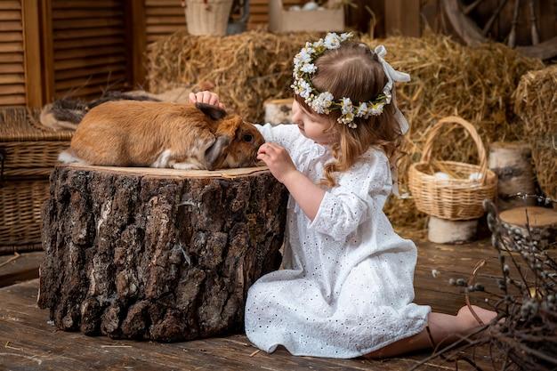 Chica rubia acariciando conejo, estilo rústico.