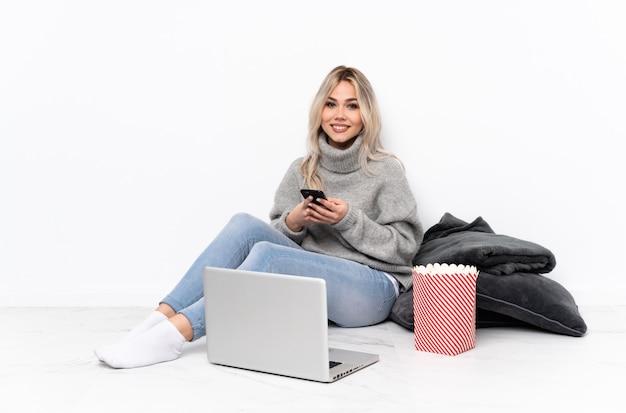 Chica rubia adolescente comiendo palomitas de maíz mientras mira una película en la computadora portátil enviando un mensaje con el móvil