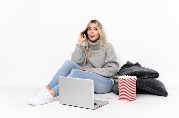 Chica rubia adolescente comiendo palomitas de maíz mientras mira una película en la computadora portátil manteniendo una conversación con el teléfono móvil