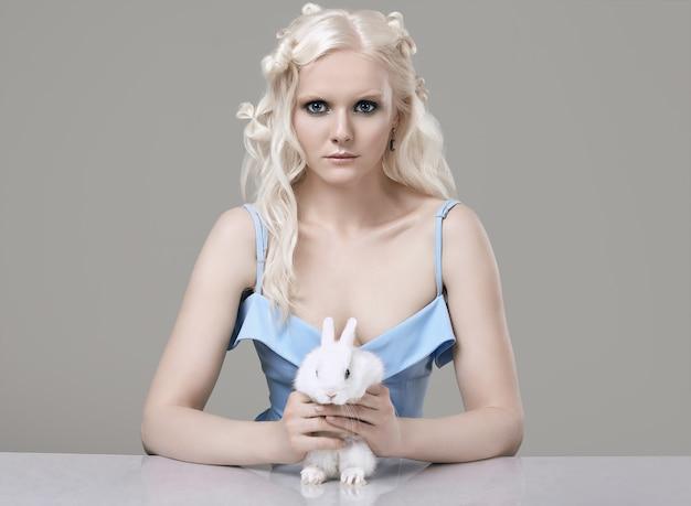 Chica rubia albina en elegante vestido posando con lindo conejito
