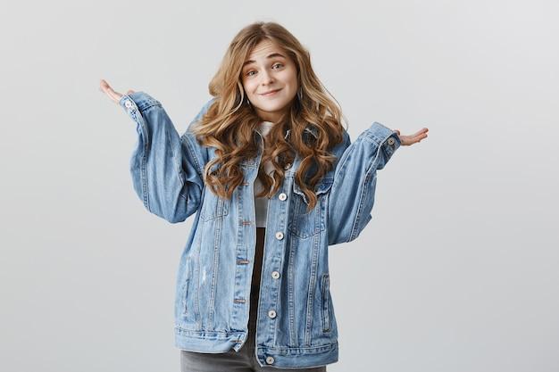 Chica rubia atractiva despistada en chaqueta vaquera, encogiéndose de hombros y sonriendo, no sé nada