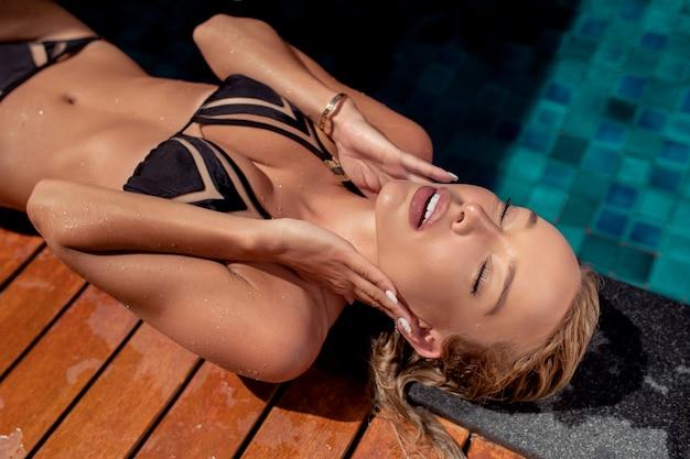 Chica rubia atractiva joven atractiva en traje de baño negro que toma el sol mientras que descansa sobre una cama del tablón cerca de la piscina. vacaciones de playa y relajación de verano. sonrisa dentuda