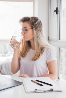 Chica rubia bebiendo agua en el trabajo