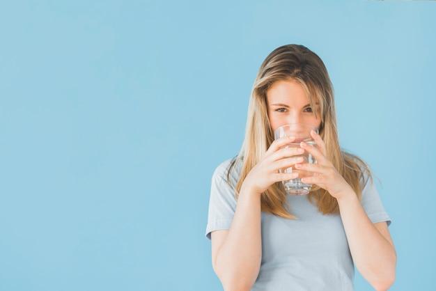 Chica rubia bebiendo vaso de agua