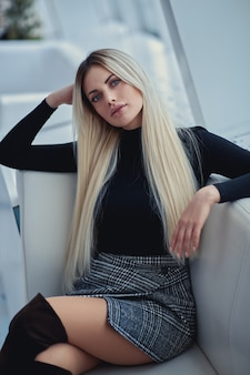 Chica rubia de belleza en el café con ropa de estilo