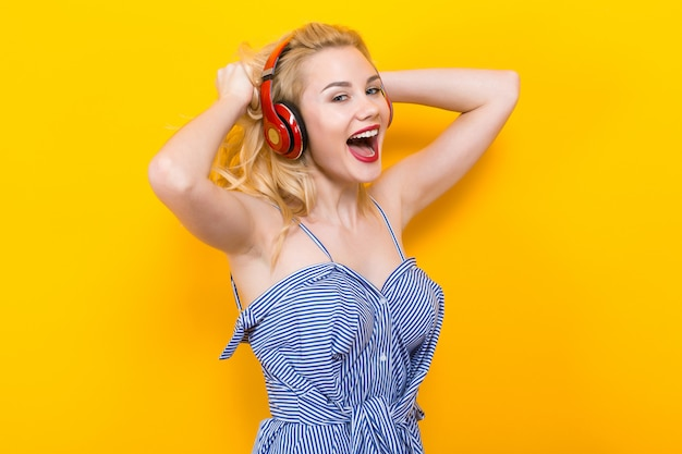 Chica rubia en blusa azul a rayas con auriculares