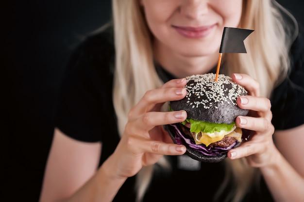 Chica rubia con una camiseta negra con una gran hamburguesa negra en sus manos