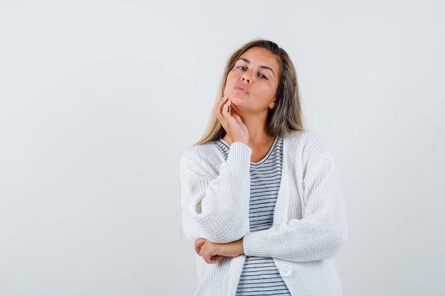 Chica rubia con camiseta a rayas, cárdigan blanco y pantalones de mezclilla apoyando la barbilla en la mano mientras sostiene una mano debajo del codo y se ve atractiva, vista frontal.