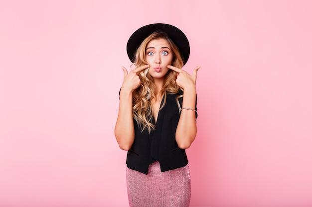 Chica rubia con cara de sorpresa de pie sobre la pared rosa. vestido elegante con lentejuelas. emociones asombradas.