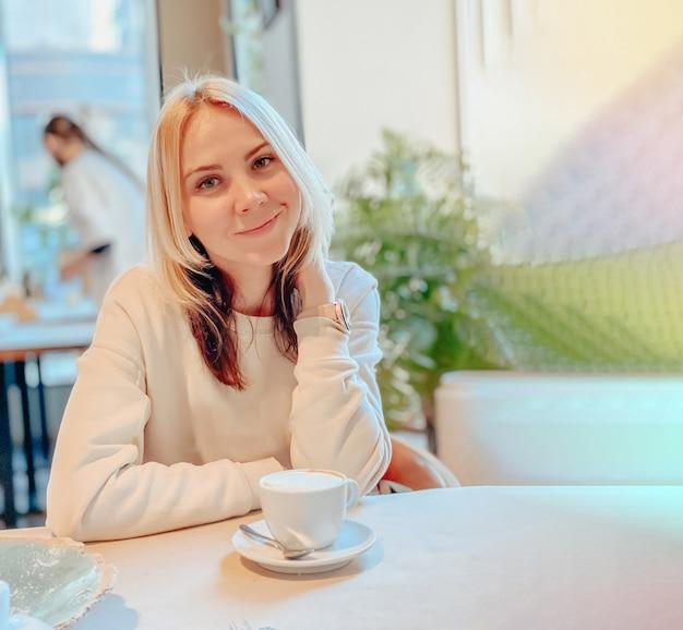 Una chica rubia caucásica alegre con un suéter ligero se sienta en un restaurante cerca de la ventana en una mesa