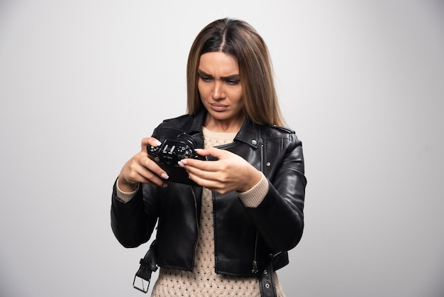 Chica rubia con chaqueta de cuero negro revisando su historia fotográfica en dslr y parece insatisfecha.