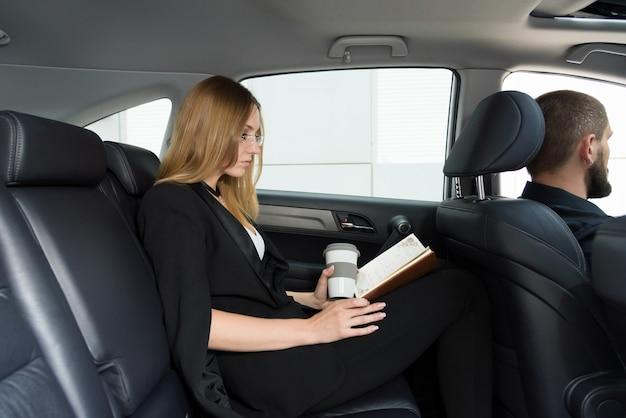 Chica rubia en un coche con un conductor en el asiento trasero con una taza y un cuaderno