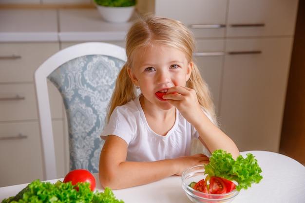 Chica rubia en la cocina comiendo verduras, nutrición adecuada para niños