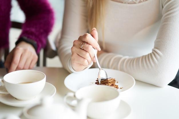 Chica rubia comiendo pastel en café