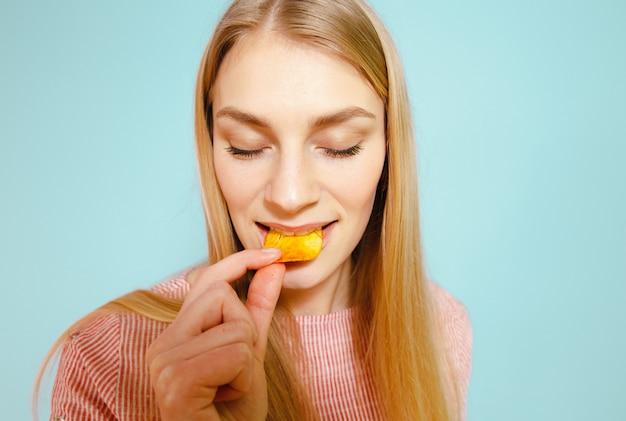 Una chica rubia comiendo patatas fritas sobre un fondo azul.