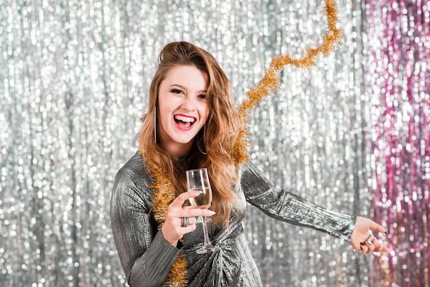 Chica rubia con copa de champagne jugando