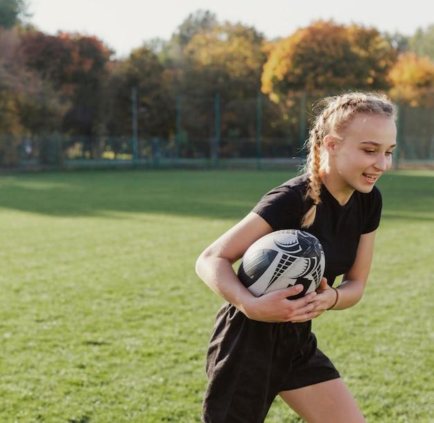 Chica rubia corriendo con una pelota de rugby