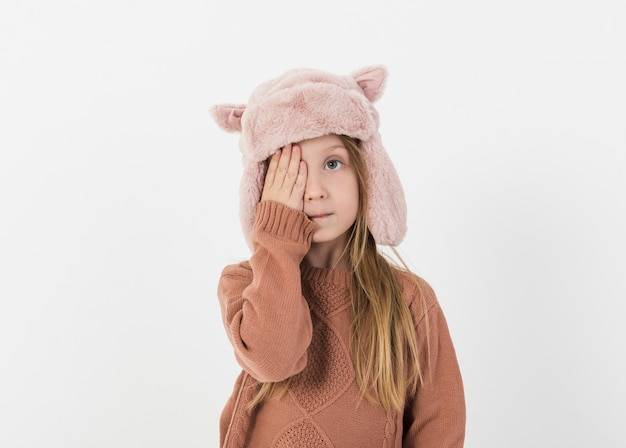 Chica rubia cubriendo la mitad de su rostro