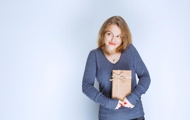 Chica rubia demostrando su caja de regalo de cartón y sintiéndose positiva.