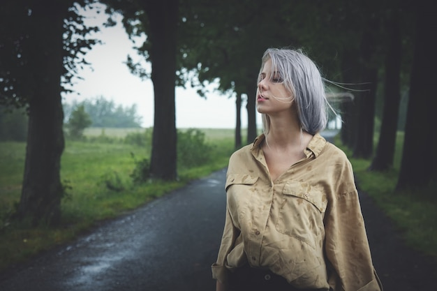 Chica rubia en depresión en el camino rural en día lluvioso