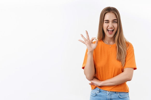 Chica rubia descarada muestra un signo bien, guiña un ojo y sonríe, asegúrate de que te gustará, la mejor elección jamás hecha.