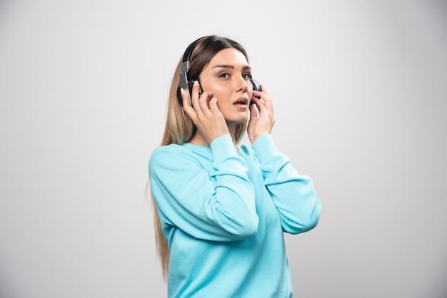 Chica rubia dj escuchando música en auriculares y no le gusta