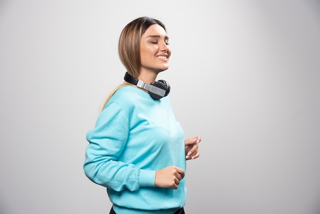 Chica rubia dj posando con auriculares de manera positiva