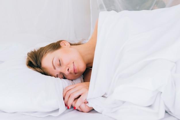 Chica rubia durmiendo en la cama