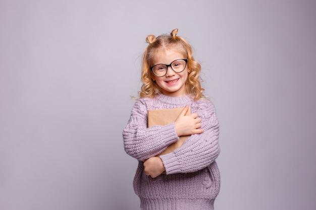 Una chica rubia en edad preescolar con gafas y un libro en sus manos está sonriendo sobre un fondo gris