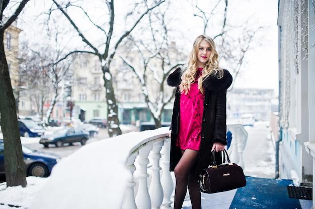 Chica rubia elegancia en vestido de noche rojo y abrigo de piel en las calles de la ciudad en día de invierno.