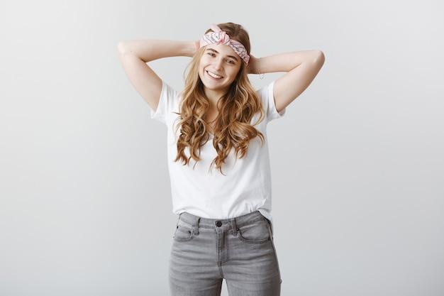 Chica rubia elegante despreocupada disfrutando del verano, mirando feliz