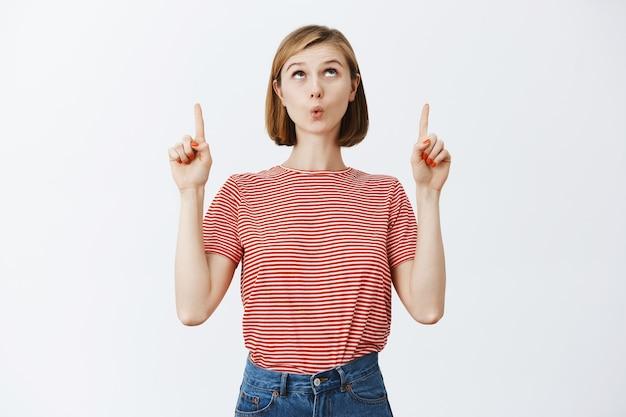 Chica rubia emocionada y divertida mostrando una promoción impresionante, mirando y señalando con el dedo