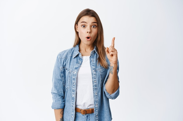 Chica rubia emocionada levantando el dedo en el signo de eureka y jadeando, sugiriendo un gran plan, encontró una solución, de pie contra la pared blanca