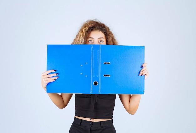 Chica rubia escondiendo su rostro detrás de una carpeta azul.