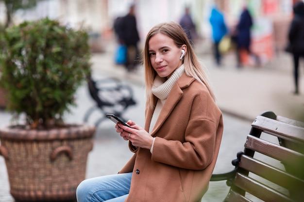 Chica rubia escuchando música con auriculares afuera