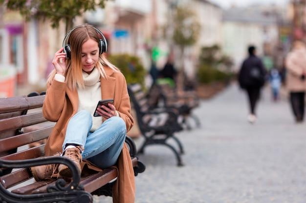 Chica rubia escuchando música en auriculares con espacio de copia