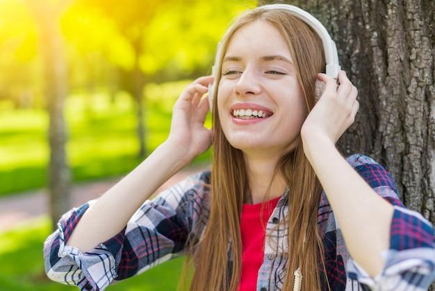 Chica rubia escuchando música con auriculares