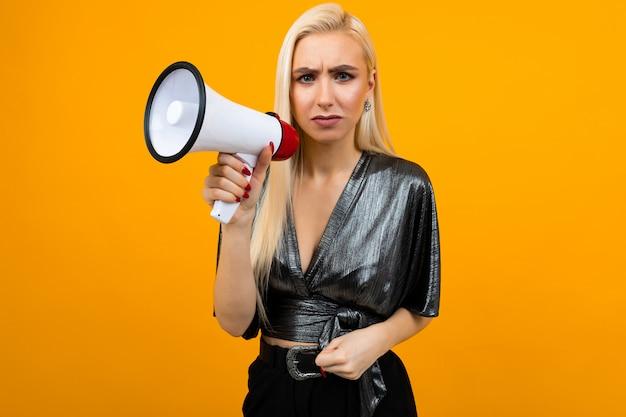 Chica rubia europea en una blusa de grafito con un megáfono en sus manos para un banner de noticias en la pared amarilla