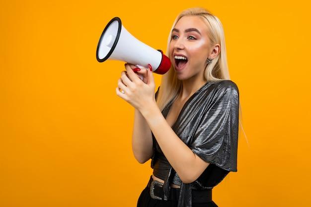 Chica rubia europea en una blusa de grafito con un megáfono en sus manos para un banner de noticias sobre una superficie de estudio amarilla
