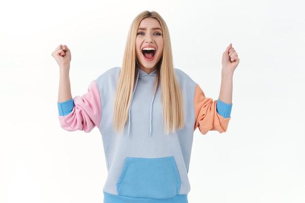 Chica rubia feliz y emocionada con sudadera con capucha, cantando, celebrando la victoria, ganando el premio, logrando la meta