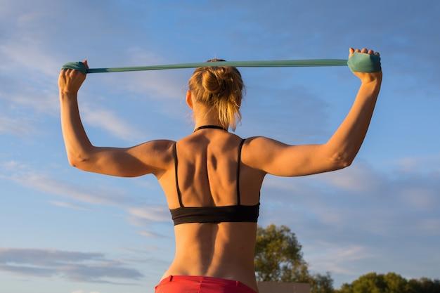 Una chica rubia con una figura deportiva en un top negro y polainas rosadas hace ejercicios en el parque