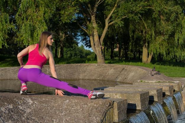 Una chica rubia con una figura deportiva en un top rosa y leggings lilas hace ejercicios en el parque