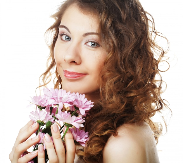 Chica rubia con flor rosa sobre fondo blanco.