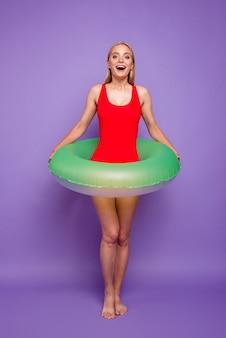 Chica rubia con flotador verde alrededor de la cintura aislado en púrpura