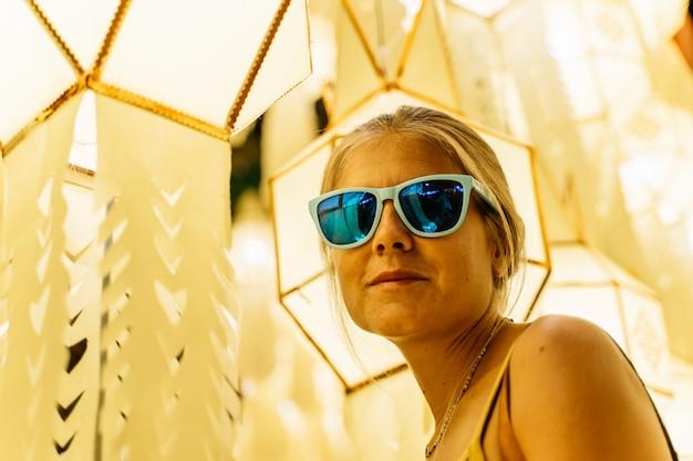Chica rubia con gafas de sol rodeada de farolillos chinos en la noche