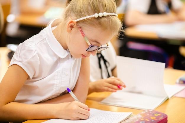 Chica rubia con grandes gafas sentado en el aula, estudiando, sonriendo. educación en la escuela primaria, primer día en la escuela.