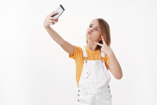 Chica rubia guapa y elegante con camiseta y mono, levantar la mano con el teléfono inteligente, tomar autofotos, fotografiar para las redes sociales en línea, mostrar el signo de la paz o la victoria, colocarse en la pared blanca